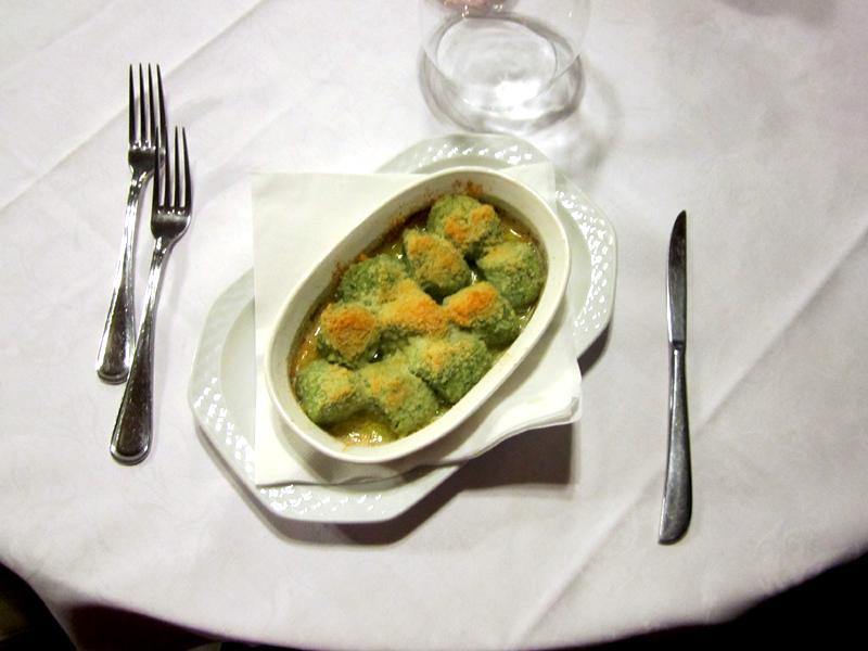 Gnudi di ricotta e spinaci gratinati al forno con burro e formaggio.